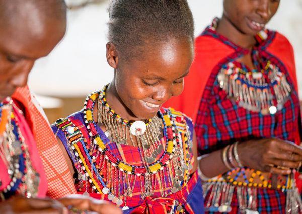 Three Maasai women smiling and beading handicrafts, Masai Mara Kenya.