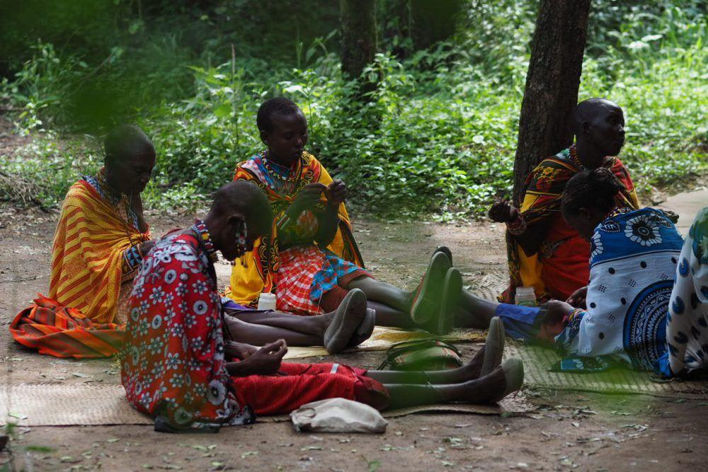 Maasai women in traditional clothing making handicrafts.