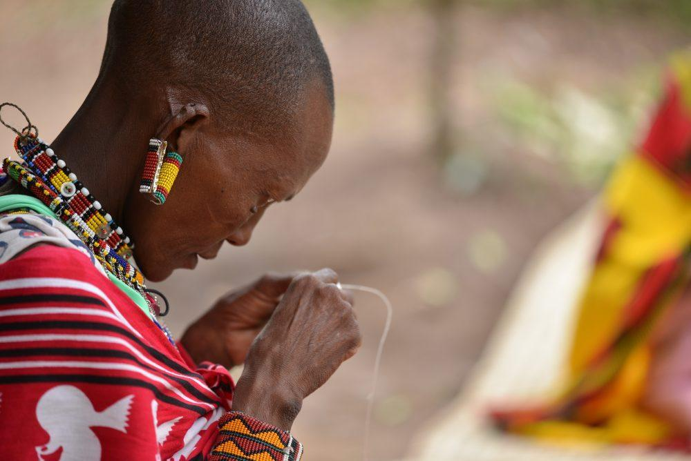 Maasai women in traditional clothes making handicrafts, Kenya.
