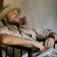 Man slouched in chair looking into the distance at Basecamp Explorer safari camp in Kenya.