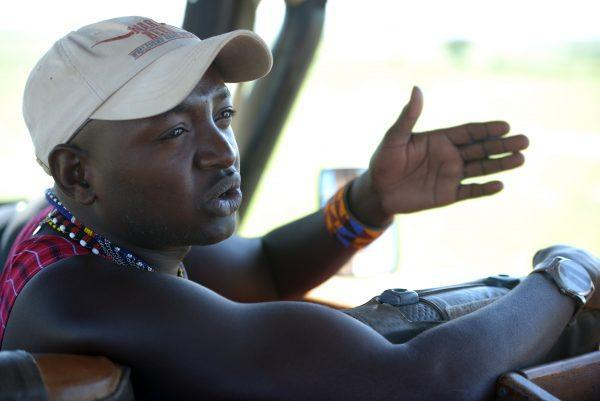 Maasai guide in safari jeep explaining to guests on Basecamp Explorer game drive.