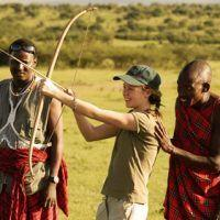 Young girl learning to use bow and arrow from Maasai in Kenya.