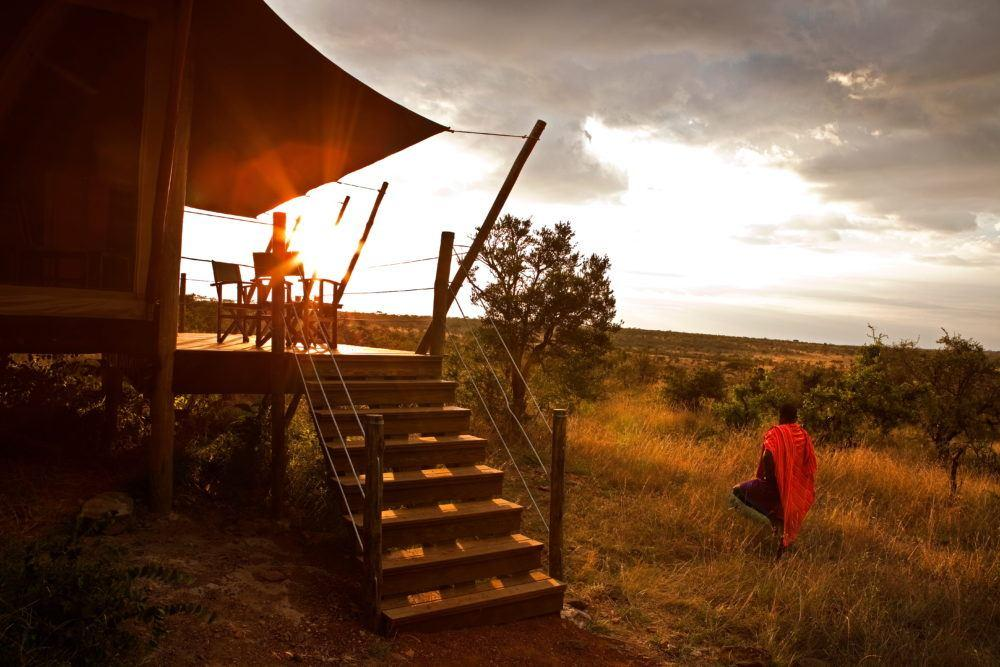 Masai standing outside guest tent looking at sunrise at Eagle View safari camp in Masai Mara.