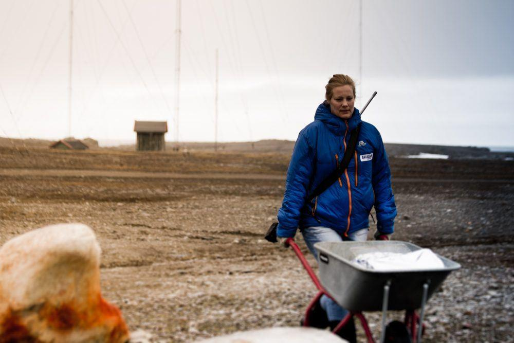 Woman with wheelbarrow at Isfjord Radio on Svalbard.