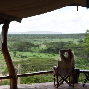 Woman sitting on terrace looking over the savannah at Basecamp Explorer Eagle View safari camp in Masai Mara, Kenya.
