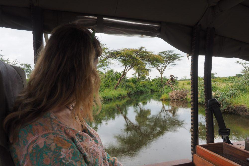 Woman sitting in safari jeep looking at river in Masai Mara, Kenya.