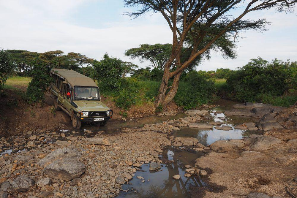 Safari jeep crossing river on a Basecamp Explorer game drive in Masai Mara, Kenya.