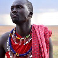 Maasai man in traditional clothes looking into the distance in Masai Mara, Kenya.