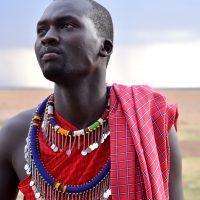 Maasai man in traditional clothes looking into the distance in Masai Mara, Kenya.