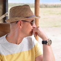 Man with straw hat on safari game drive looking into the distance.