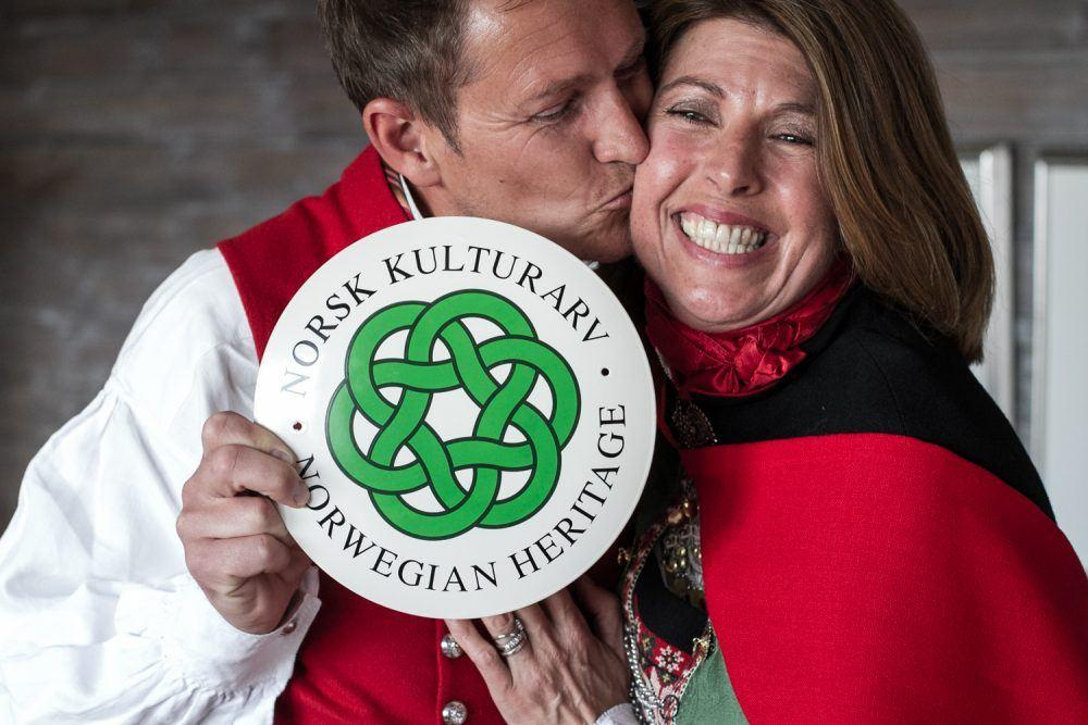 Couple kissing on cheek holding Norwegian heritage sign at Isfjord Radio.