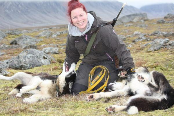 Woman sitting on grass playing with husky dogs on Svalbard.