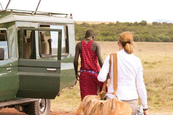 Woman with luggage following Maasai guide to safari jeep in Masai Mara.