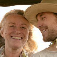 Man and woman smiling on safari in Kenya.