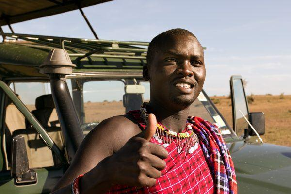Maasai guide leaning against safari jeep and giving a thumbs up.