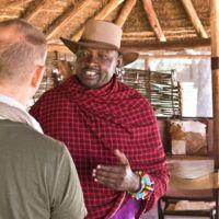 Man talking to Masai guide at Basecamp Masai Mara safari camp.