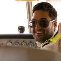 Aircraft pilot sitting in cockpit, smiling towards camera.