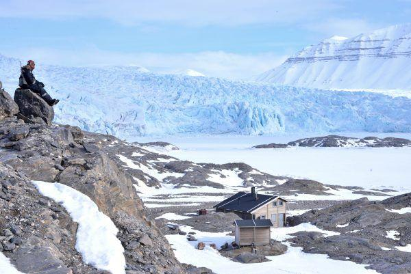 Man sitting on stone rock overlooking Basecamp Explorer Nordenskiöld Lodge in winter.