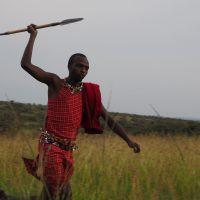 Maasai guide running and holding spear in Maasai Mara, Kenya.