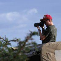 Man standing in safari jeep taking photo with digital camera on game drive in Masai Mara.