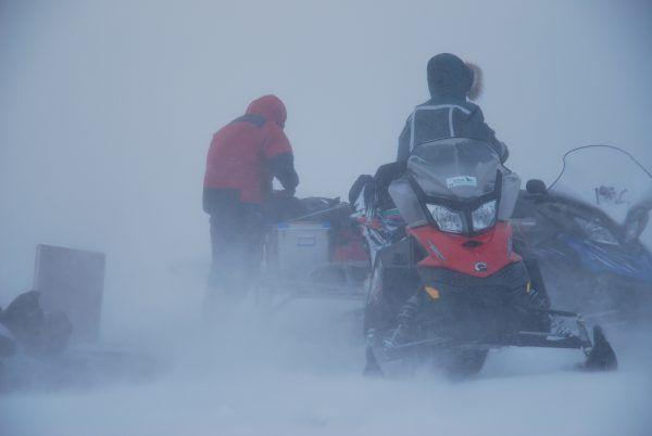 Two people snowmobiling in snowstorm at Spitsbergen.