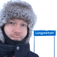 Man in snowsuit standing next to Longyearbyen sign in Spitsbergen.