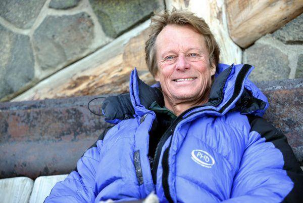 Man in blue snowsuit sitting against wall and smiling to camera.