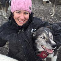 Woman with pink headband cuddling with husky dogs in Spitsbergen.