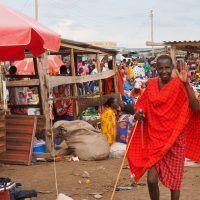 Maasai guide standing in village marketplace waving to camera.