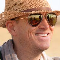 Man with straw hat and sunglasses smiling and looking into the distance.