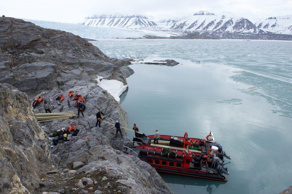 People in rib boats delivering building materials at Nordenskiöld Lodge on Svalbard.