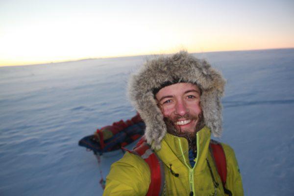 Man in snowsuit hiking in arctic landscape.