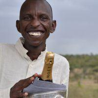 Basecamp Explorer Kenya staff member smiling with bottle of Moët.