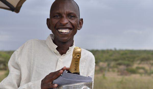 Basecamp Explorer Kenya staff member smiling with bottle of Moët.