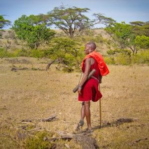 One Maasai man standing on the savannah in Masai Mara, leaning on his spear and looking out into the distance.
