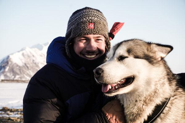 Man and husky dog smiling with arctic mountains in the background.