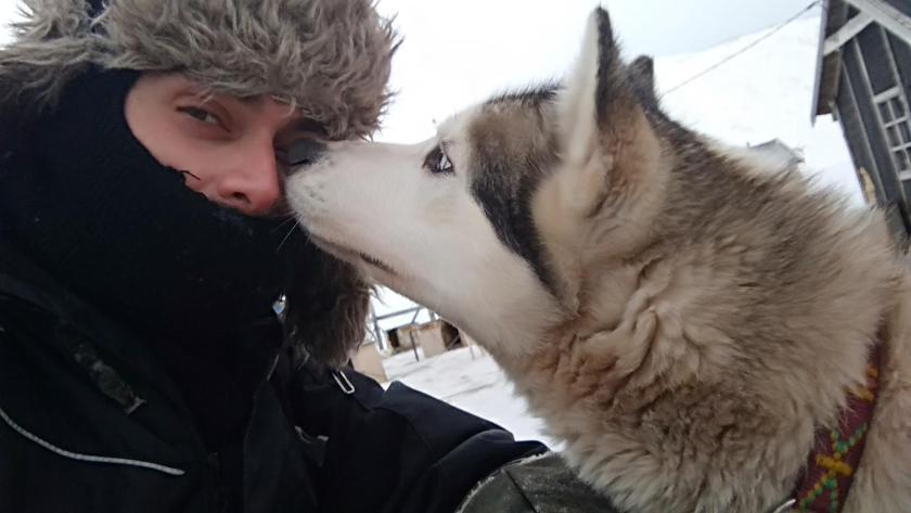 Woman being sniffed in the face by a husky dog on Svalbard.