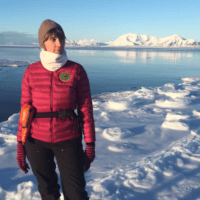 Woman standing on floating glacial ice in Svalbard.