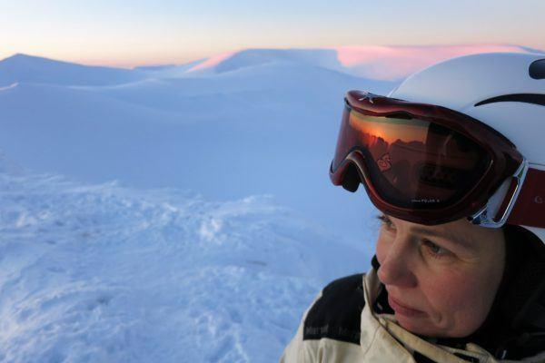 Woman with helmet and snow glasses looking into the distance with arctic mountains in the background.