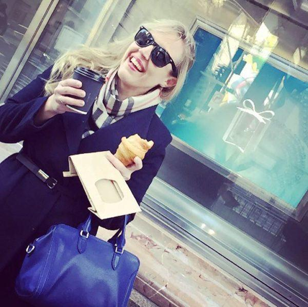 Fashionable woman with sunglasses laughing and holding coffee.