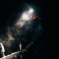 Man dogsledding with headlight in snowstorm on Svalbard.