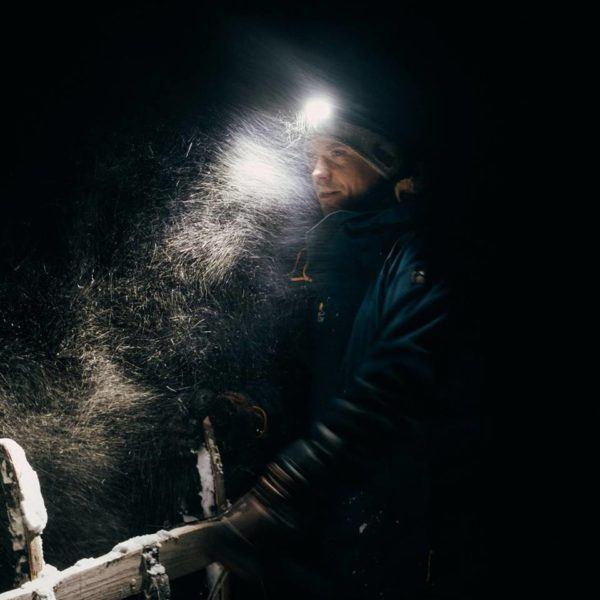 Man dogsledding with headlight in snowstorm on Svalbard.