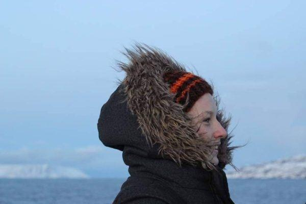 Woman with winter hood looking into the distance on Svalbard.