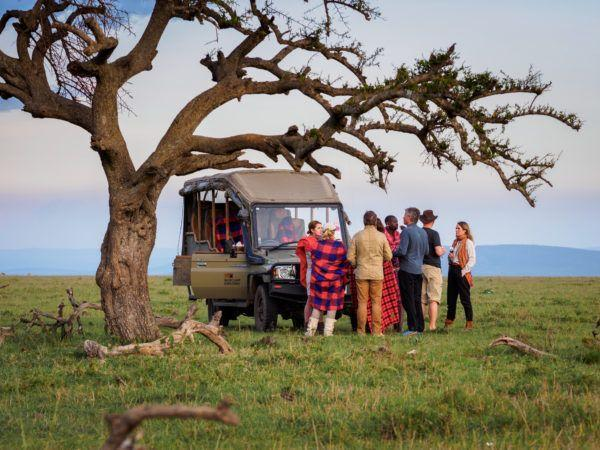 Tourist group on safari game drive standing under tree next to their jeep on the savannah in Masai Mara.
