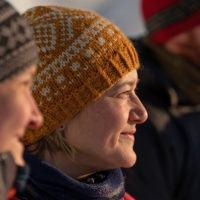 Portrait photo of woman with knitted hat looking into the distance.