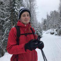 Man with red winter coat and skis smiling to camera.