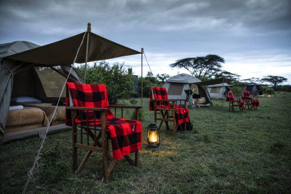 View of tents in Basecamp Explorer Dorobo Mobile camp with red blanket chairs in Masai Mara, Kenya.