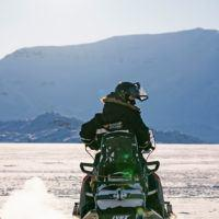 Person in Basecamp Explorer snowsuit with helmet driving a snowmobile in Spitsbergen.