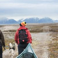 Two women hiking in arctic tundra with husky dog and kayak on Svalbard.
